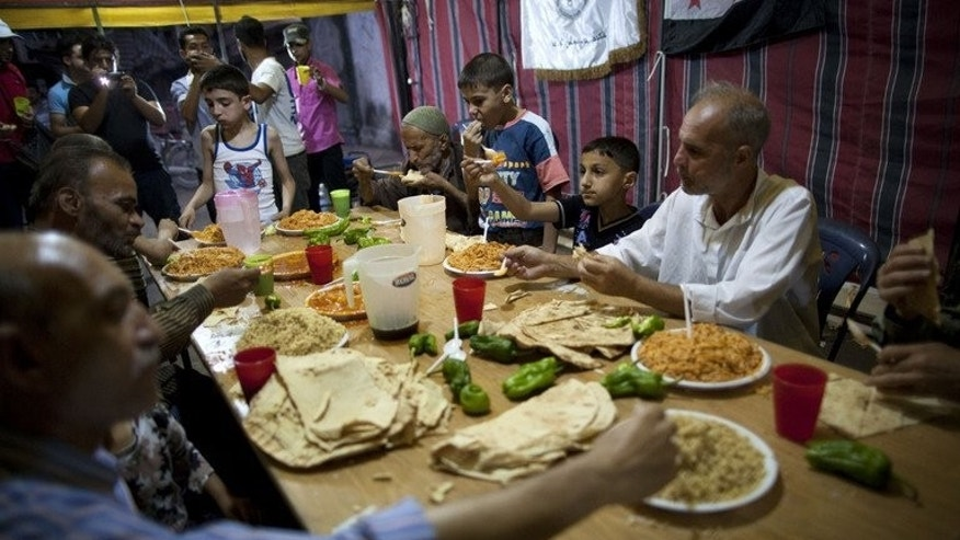People eat a charity iftar meal in Bustan al-Qasr district of Aleppo on July 11. As Syria's Muslims observe the fasting month of Ramadan at a time of war for a third year running, many people are turning to black humour to help them cope.