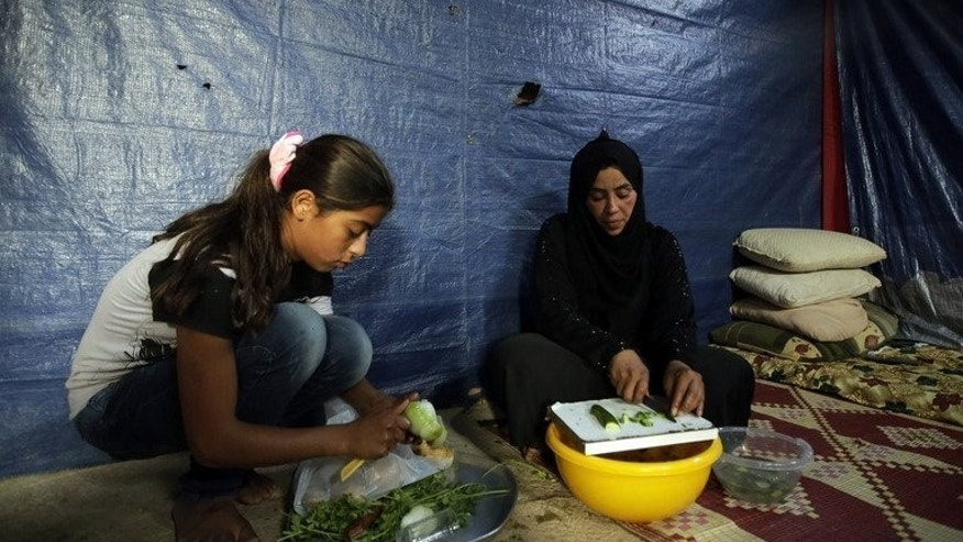 Fatima (right) a refugee widow from Homs, prepares an iftar meal with her daughter in Tripoli, Lebanon, on July 15. Burdened by inflation and security problems on the roads, housewives are now making more food at home and relying less on buying special Ramadan sweets from the shops.