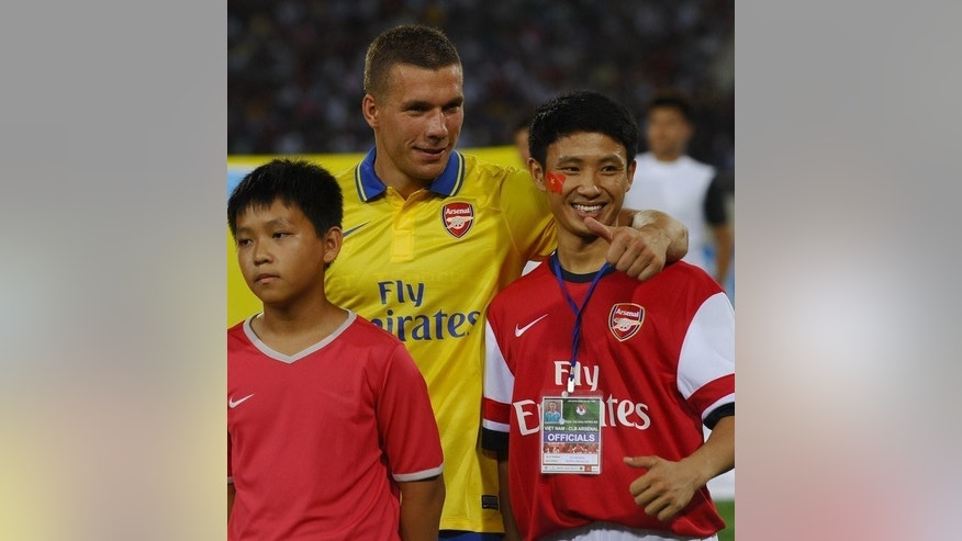 "Vu Xuan Tien (R), a Vietnamese Arsenal fan dubbed the ""Running Man"", poses with Lukas Podolski on July 17, 2013. Tien says that he has been invited to watch his heroes play in London."