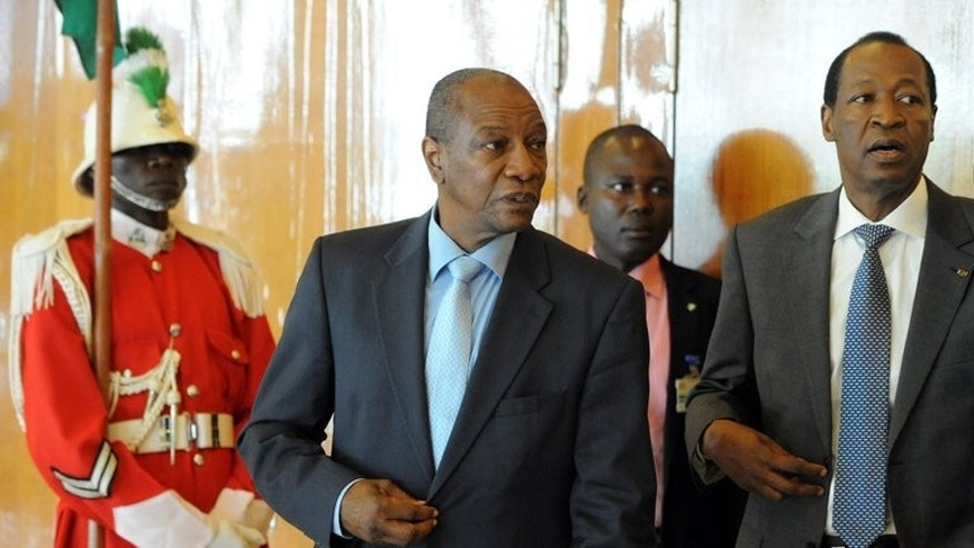 Guinean President Alpha Conde (C) chats with his Burkinabe counterpart Blaise Compaore (R) during an ECOWAS summit in the Nigerian capital Abuja on July 18, 2013. West African leaders on Thursday insisted Mali's presidential election would be held on July 28 as scheduled despite doubts over whether the crisis-hit nation was ready to organise a vote.