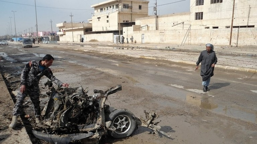 An Iraqi policeman inspects the debris of a vehicle following a blast in Baquba, capital of Diyala province, on February 23, 2012. A bomb exploded in a crowded mosque north of Baghdad on Friday afternoon, killing at least 20 people and wounding 40, police said.