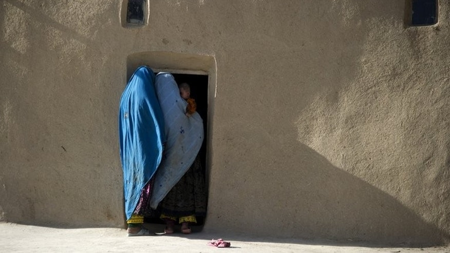 Two Afghan women and a baby gather in a doorway on September 8, 2011, in the village of Barnes in the province of Paktika. A bomb killed five young children and a woman when it exploded after being made at the home of a Taliban commander in eastern Afghanistan, a government official said Friday.