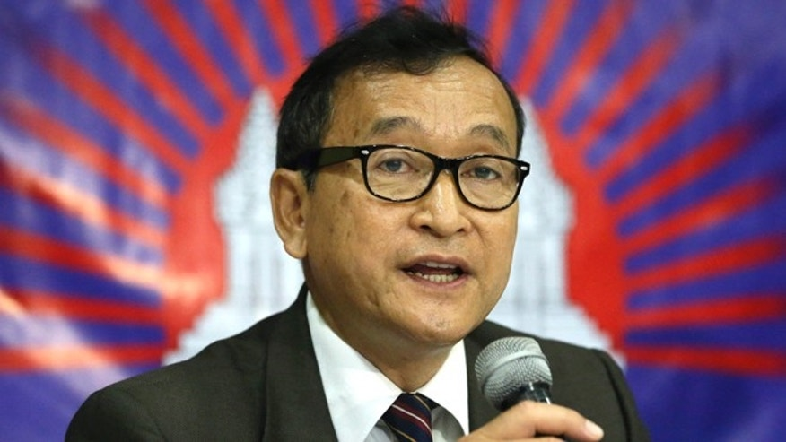 In this Sept. 10, 2012 file photo, Cambodian opposition leader Sam Rainsy, who was currently living in exile in France, talks about the opposition's plans for 2013 elections in Cambodia during the launching of the International Parliamentary Committee for Democratic Elections in Cambodia with Philippine Sen. Franklin Drilon in San Juan, east of Manila, Philippines.
