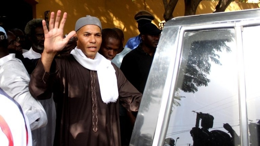 The son of former Senegalese leader Abdoulaye Wade, Karim, waves while being arrested on April 2013 in Dakar. A court ruled his rights were not violated.