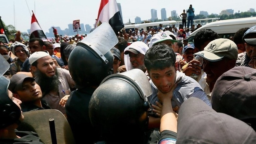 A supporter of Egypt's ousted president Mohamed Morsi is held back by riot policemen during a rally in Cairo on July 17, 2013. The interim government tasked with putting Egypt back on track after president Morsi's ouster faces enormous challenges, from fixing the shattered economy to restoring security and democracy, experts say.