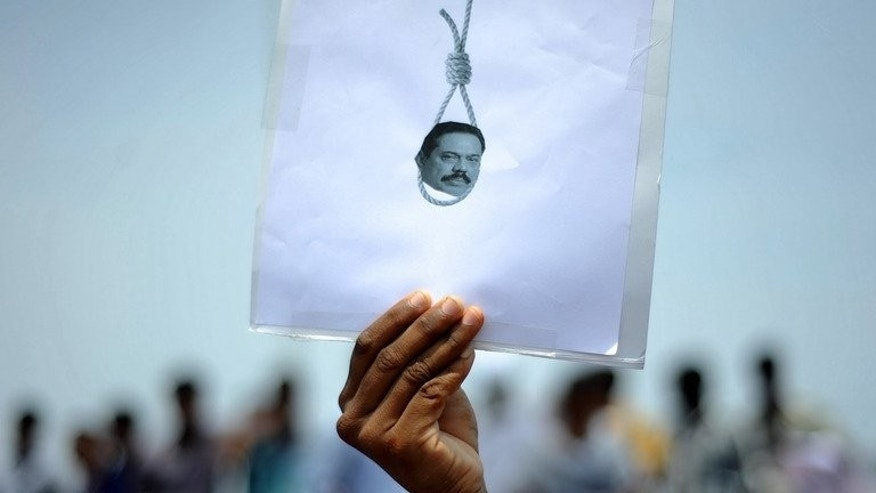 A student holds a poster featuring Sri Lanka's president in a protest over alleged war crimes against Tamils in Sri Lanka, in Chennai, India on March 20, 2013. European parliamentarians Friday asked Sri Lanka to deliver on promises to investigate allegations of war crimes and ensure ethnic reconciliation more than four years after crushing Tamil separatists.