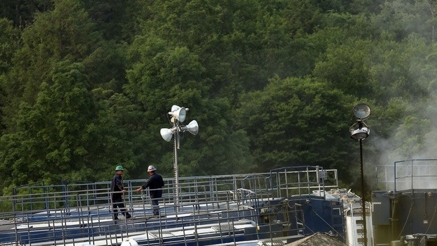 "Men work on a natural gas valve at a hydraulic fracturing site on June 19, 2012 in South Montrose, Pennsylvania. The government presented tax breaks for energy fracking companies to create the world's ""most generous"" regime for shale gas extraction."