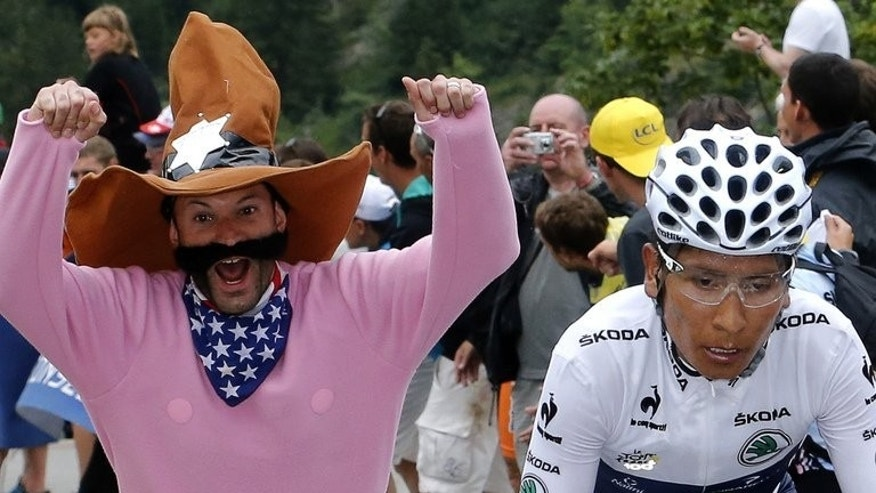 A supporter cheers on Nairo Quintana (right) during the Tour de France 18th stage at Alpe d'Huez on Thursday. The Colombian climber is on course to win the white jersey for the best young rider but is also eager to catch Chris Froome in the race to win the polka dot jersey for the King of the Mountains.