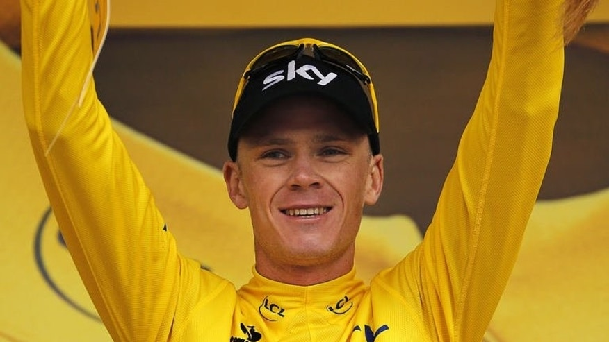 Britain's Chris Froome celebrates his overall leader yellow jersey on the podium at the end of the 19th stage of the 100th edition of the Tour de France cycling race on July 19, 2013 between Bourg-d'Oisans and Le Grand-Bornand, French Alps.