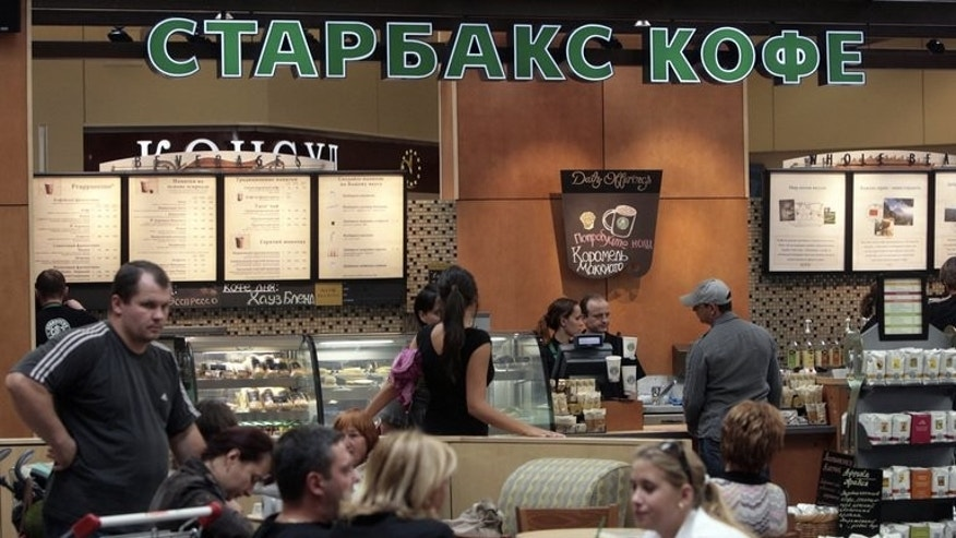 Customers drink coffee on the opening day of Russia's first Starbucks in Moscow in September 2007. Starbucks will be among companies in the spotlight at the OECD meeting in Moscow for booking profits in low-tax countries.