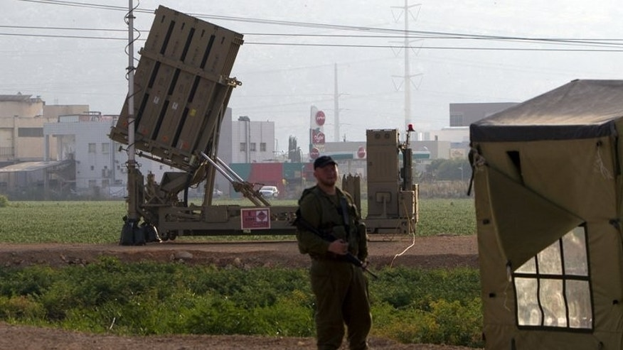 "An Israeli soldier stands in front of an ""Iron Dome"" short-range missile defence system near the northern Israeli city of Haifa on May 6, 2013. Israel deployed its Iron Dome missile defence system near the Red Sea resort of Eilat, which is close to the border with Egypt, an army spokeswoman said."