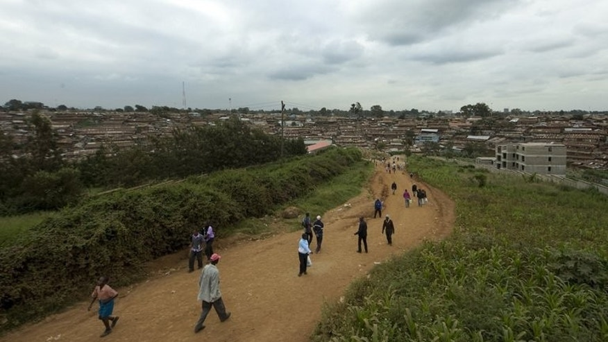 People walk on a road leading to Kibera in Kenya last year. As Britain's Chris Froome pedals towards Tour de France victory, far away in his birthplace of Kenya he is being cheered on by the cyclist who first trained him.