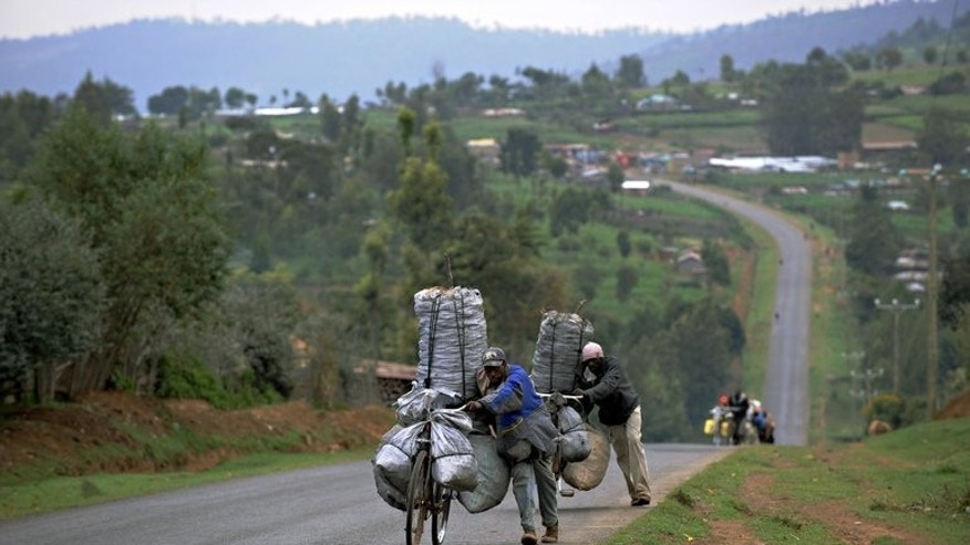 Men wheel bicycles loaded with charcoal bags up a hill on a road in Kenya in 2009. David Kinjah pushed young Chris Froome as he developed his cycling strength pedalling on back roads in the hills and coffee farms around the capital Nairobi, one of the highest altitude capitals in the world.