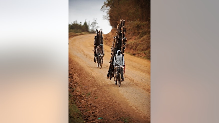 "Men take forest wood to town along a road in Kenya in September 2009. ""Training together in the rural highlands north of Nairobi is what ignited the passion for cycling which (Chris) Froome has today,"" the cyclist's website reads."