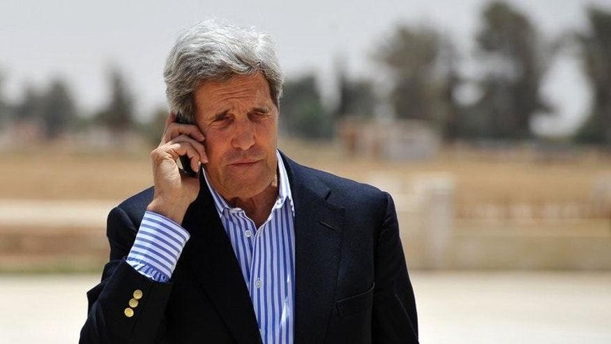 US Secretary of State John Kerry speaks on the phone at Mafraq air base before boarding a helicopter to Amman, after visiting Zaatari refugee camp in Jordan on July 18, 2013. Kerry Friday met with chief Palestinian negotiator Saeb Erakat in a final push to get a peace bid back on track before heading home.