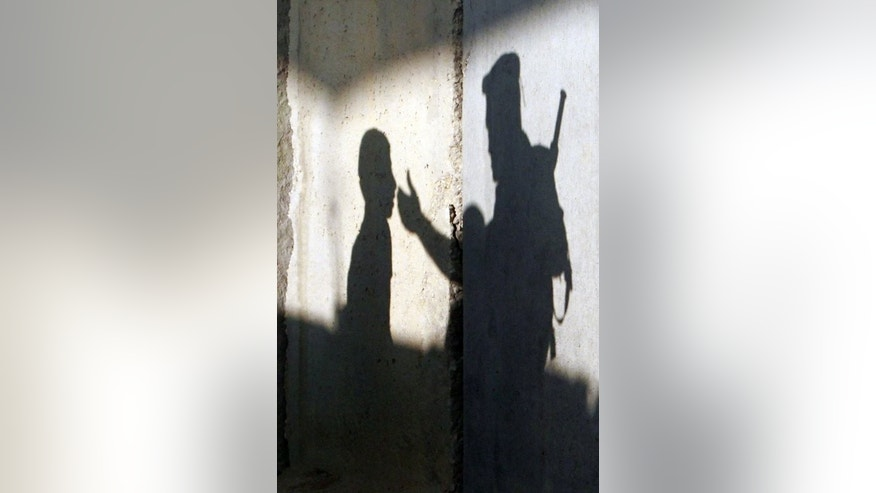 The shadow of a member of the Israeli security forces gesturing towards a Palestinian youth is seen on a wall of a checkpoint on the outskirts of the West Bank town of Bethlehem on July 19, 2013. US Secretary of State John Kerry Friday met with chief Palestinian negotiator Saeb Erakat in a final push to get a peace bid back on track before heading home.