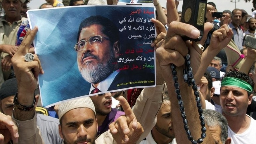 "A demonstrator holds up a portrait of deposed Egyptian president Mohamed Morsi during a rally of Hamas supporters outside the Al-Aqsa mosque in Jerusalem on July 19, 2013. Demonstrators held posters with Morsi's picture and chanted ""Morsi is the Egyptian president, Sisi is an American collaborator""."