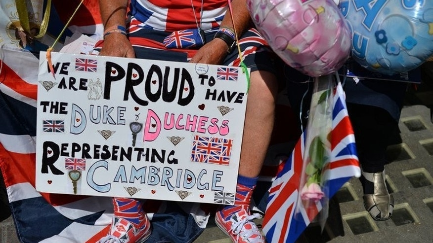 A man holds a placard as he waits outside the Lindo Wing of St Mary's Hospital, on July 18, 2013. The Duchess of Cambridge lives a very different life to most mums-to-be, but Britain's army of mothers has been captivated by her pregnancy -- and is ready to rally around to help her bring up the new heir
