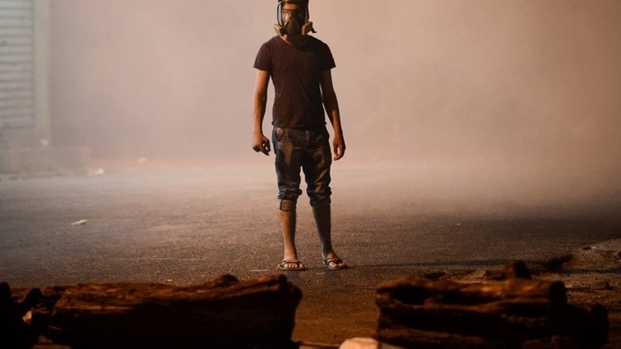 A Bahraini protester wearing a gas mask stands amid tear gas fired by riot police during clashes in the village of Diraz, west of Manama, in the early hours of July 19, 2013. Bahraini security forces clashed with anti-regime protesters early Friday, leaving several people wounded including a policeman who was shot with a home-made gun, the interior ministry and witnesses said.