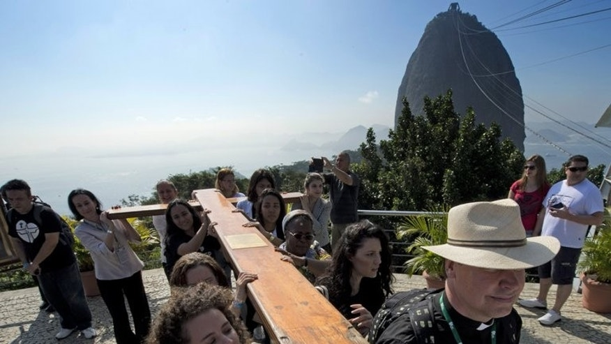 Catholics carry the World Youth Day Cross on their way up to the Sugar Loaf hill in Rio de Janeiro, Brazil on July 17, 2013. Pope Francis will portray his Catholic Church as a simple, caring institution and champion of the poor when he arrives in Brazil next week -- a country that is witnessing an evangelical Protestant surge.