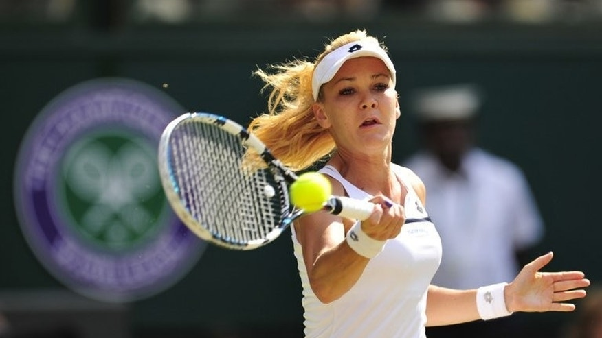 Poland's Agnieszka Radwanska returns during a match at the All England Club in Wimbledon, southwest London, on July 4, 2013. Radwanska on Friday defended her controversial nude photo-shoot which saw her dropped by a Catholic youth movement, claiming the pictures were in good taste.