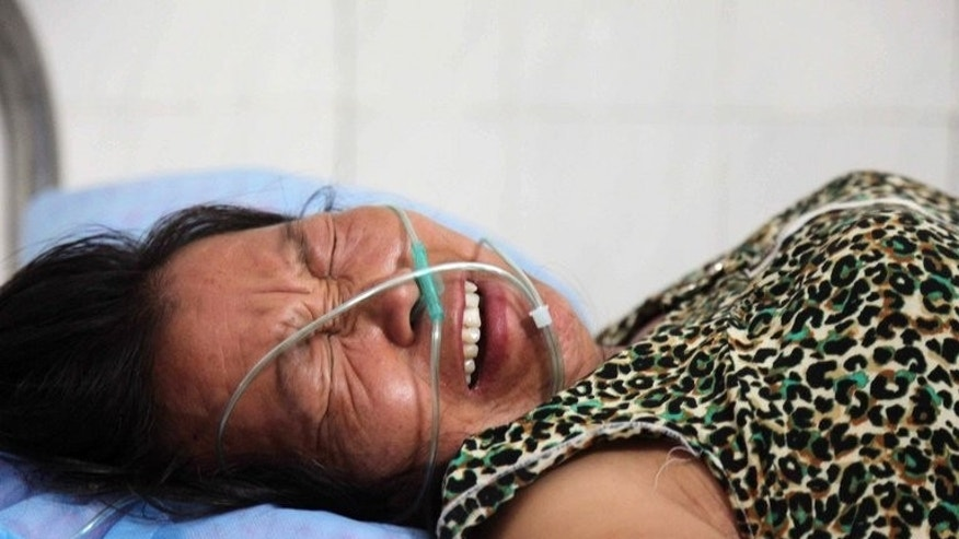 The wife of the deceased fruit seller Deng Zhengjia cries on a hospital bed in Linwu county, central China's Hunan province, on July 17, 2013. Six Chinese local government employees involved in a dispute that saw a roadside watermelon seller die have been detained, state media reported Friday as outrage over power abuses mounted.