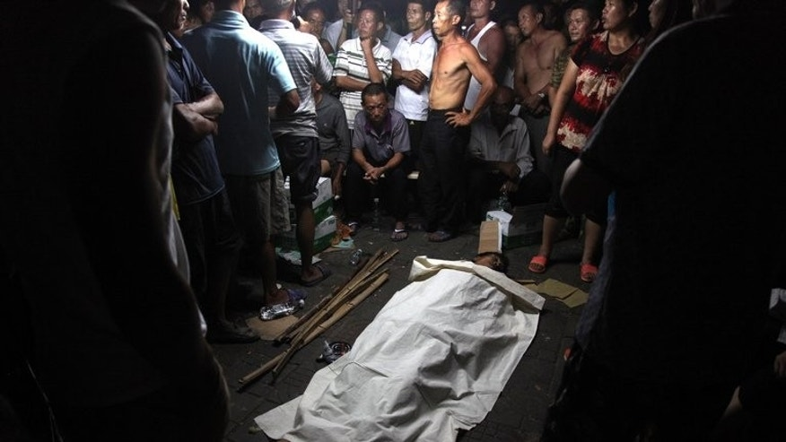 People guard the body of fruit seller Deng Zhengjia in Linwu county, central China's Hunan province, on July 17, 2013. Six Chinese local government employees involved in a dispute that saw a roadside watermelon seller die have been detained, state media reported Friday as outrage over power abuses mounted.