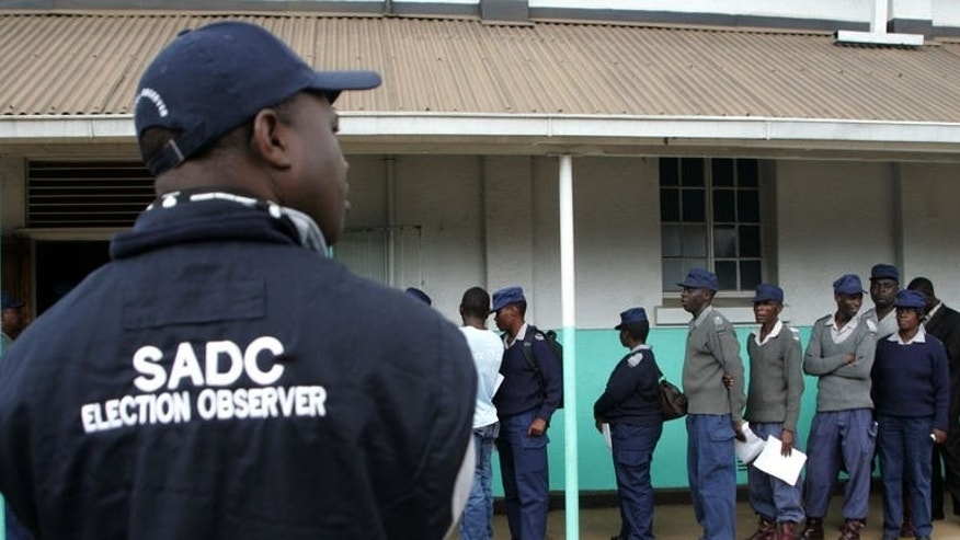 A SADC (Southern Africa Development Community) election observer looks on as Zimbabwe security forces queue to vote during early polling in Harare on July 14, 2013. South Africa's chief envoy on Zimbabwe's political crisis has conceded there are challenges in the run-up to key polls, a day before regional mediators meet to discuss the vote.