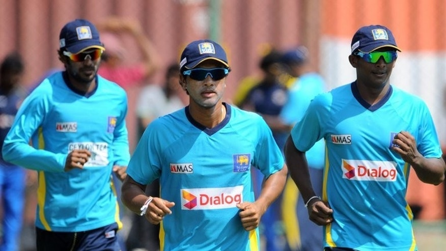 Sri Lanka captain Dinesh Chandimal (C), Ajantha Mendis (R) and Upul Tharanga (L) warm up during a practice session in Colombo on July 19, 2013. Chandimal, 23, will lead the Islanders in the first two matches against South Africa after regular captain Angelo Mathews was handed a two-match ban for his team's slow over-rates in the tri-series.