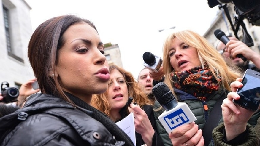 Exotic dancer Karima El-Mahroug (centre), nicknamed Ruby the Heart Stealer, speaks to journalists in Milan. The verdict in a trial against three of Silvio Berlusconi's associates for allegedly procuring prostitutes for the former Italian premier -- including the then underage Ruby -- is expected later Friday.