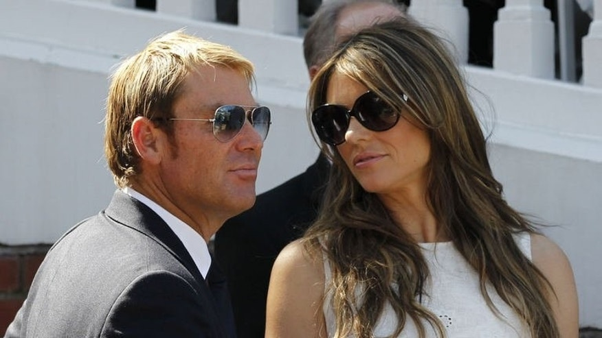 Australian former cricketer Shane Warne (L) with his fiancee British actress and model Liz Hurley are seen after he is presented with an award during the tea interval on the second day of the second Ashes cricket test match between England and Australia at Lord's cricket ground in north London, on July 19, 2013.