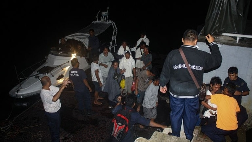 This photo, released by the Malaysian Maritime Enforcement Agency on July 18, 2013, shows passengers who were rescued from an overturned boat near Tanjung Sedili, Johor, southern Malaysia. An Indonesian woman died and seven other people remain missing after a wooden boat, believed to be smuggling them out of Malaysia, overturned.