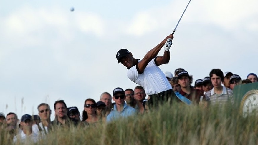 Tiger Woods tees off on the 15th hole during the British Open at Muirfield on Thursday. Tournament favourites Woods and Phil Mickelson were tied on 69, two shots off the lead, after the first day.