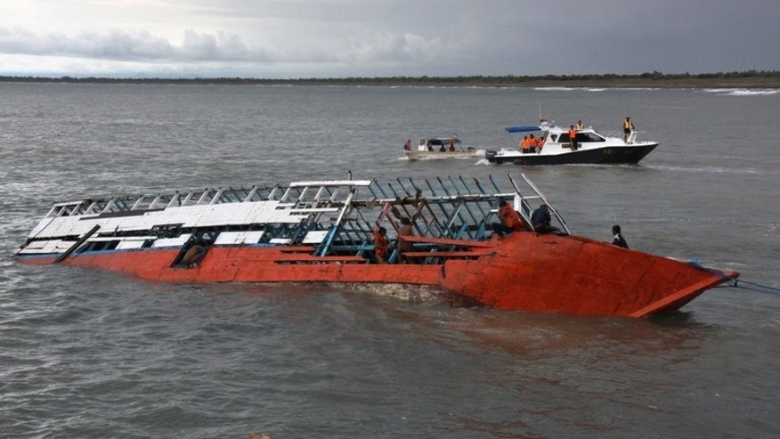 In this file photo, rescuers check the wreckage of a people smuggler's boat seen half submerged after being towed near the coast of Puger village in East Java province, on December 21, 2011. Australia said on Sunday it would pay rewards of up to $180,000 for information leading to the conviction of people-smugglers, as it defended its tougher approach on asylum-seekers.
