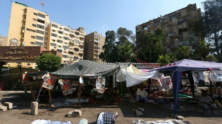 Supporters of the Muslim Brotherhood and Egypt's ousted president Mohamed Morsi, sit in tents erected in the shadow of residential buildings outside Rabaa al-Adawiya mosque in Cairo on July 18, 2013. Tensions have risen between the protesters and local residents, who are starting to complain of the continuous noise, dirt and smell.