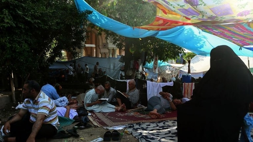 Supporters of the Muslim Brotherhood, rest under makeshift tents erected outside Rabaa al-Adawiya mosque in Cairo on July 18, 2013. Some of those living around Rabaa al-Adawiya have taken a dim view of the protesters, a significant number of whom are camped on the small grass squares outside their apartment blocks.