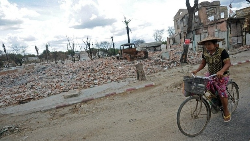 A local resident is seen riding her bicycle past the ruins of destroyed buildings in riot-hit Meiktila, central Myanmar, on June 4, 2013. Myanmar has lifted a state of emergency imposed in the riot-hit area in March where dozens of people were killed in religious violence.