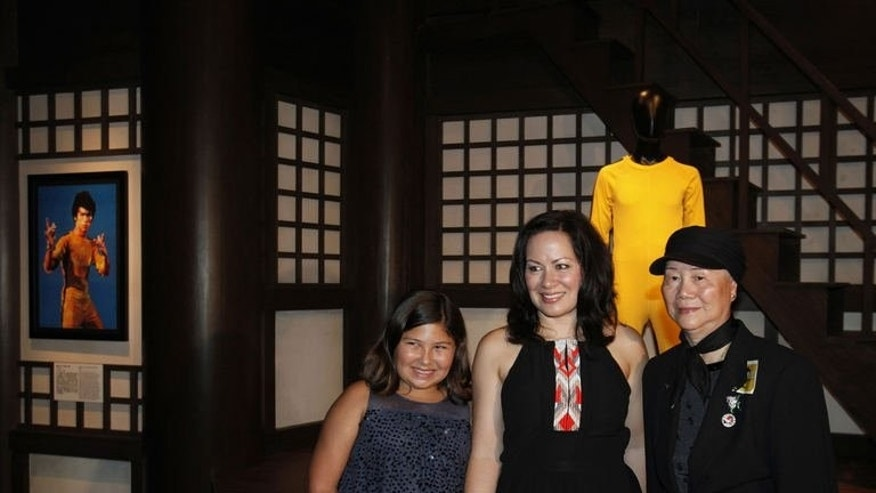 Shannon Lee (C), daughter of the late Kung Fu legend Bruce Lee, poses for a photo with her 10-year-old daughter Wren (L) and Phoebe, elder sister of Lee, at the Hong Kong Heritage Museum during the opening of a five-year exhibition on the martial arts icon, on July 19, 2013. The exhibition features memorabilia from his life and films, including his famous yellow jumpsuit.