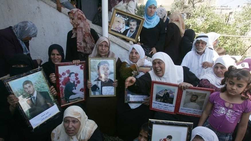 "Female relatives of Palestinians jailed in Israeli prisons hold up their pictures during a demonstration in Gaza City, on July 9, 2007. Israel has announced it will release some Palestinian prisoners as a ""gesture"", as the two sides agreed to meet to pave the way for their first direct talks in three years."