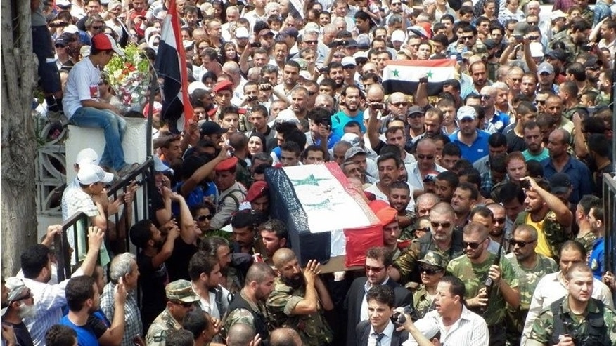 Friends and relatives of Mohammad Darrar Jamo carry his coffin during a funeral procession in Latakia province, western Syria, on July 19, 2013. Jamo, a Syrian who has lived in Lebanon for 25 years, was murdered by armed men early on July 17, in front of his house in Sarafand in the south of Lebanon.