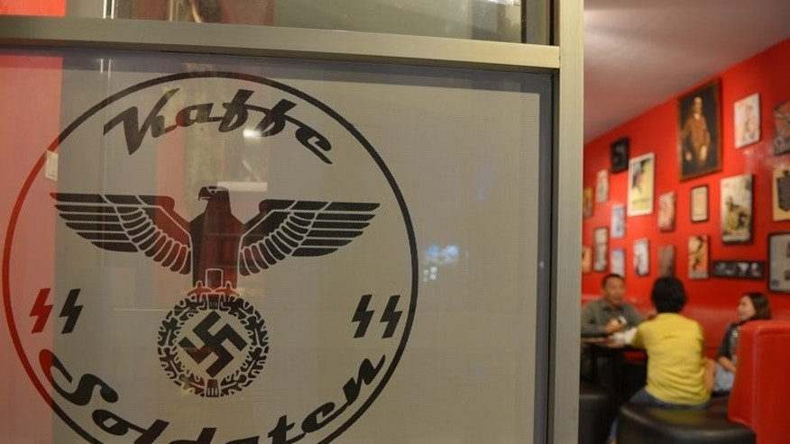 Customers have dinner at the SoldatenKaffee in Bandung on July 16, 2013. When the cafe opened in 2011 no one voiced offence at the waiters and guests dressed as Nazi soldiers.
