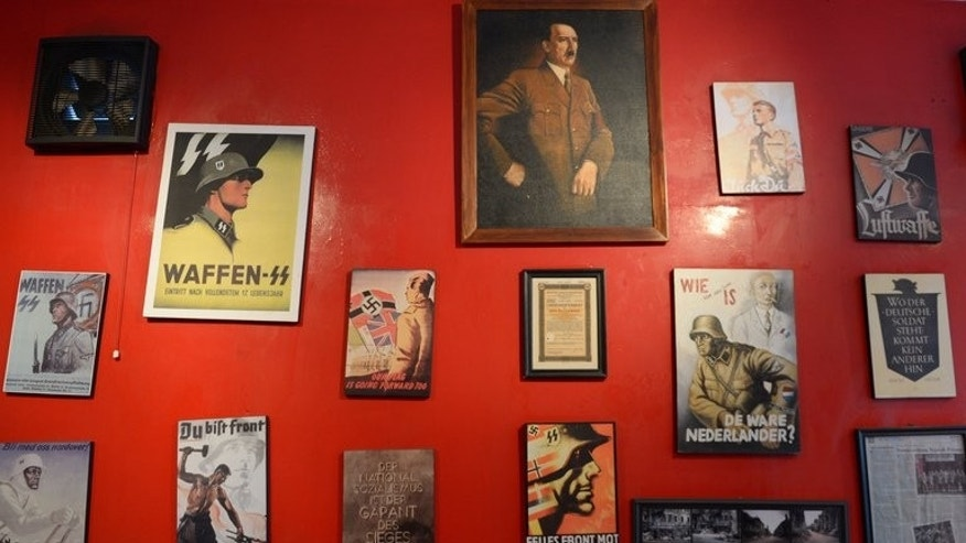 "Images of Adolf Hitler and German soldiers decorate a wall at the SoldatenKaffee in Bandung, Indonesia, on July 16, 2013. ""The Soldiers' Cafe"" opened its doors in the western Javanese city in 2011. From a painting hung high on a blood-red wall, Adolf Hitler peers down on young students eating schnitzel and slurping German beer in Indonesia's Nazi-themed cafe. AFP PHOTO / ADEK BERRY"