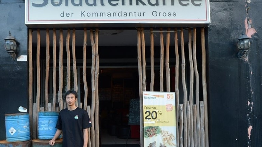 "This picture taken on July 16, 2013 shows owner Henry Mulyana outside his ""Soldiers' Cafe"" in Bandung, Indonesia. The restaurant had only ever received positive press before the recent exposure in English-language media and receives a regular stream of customers."