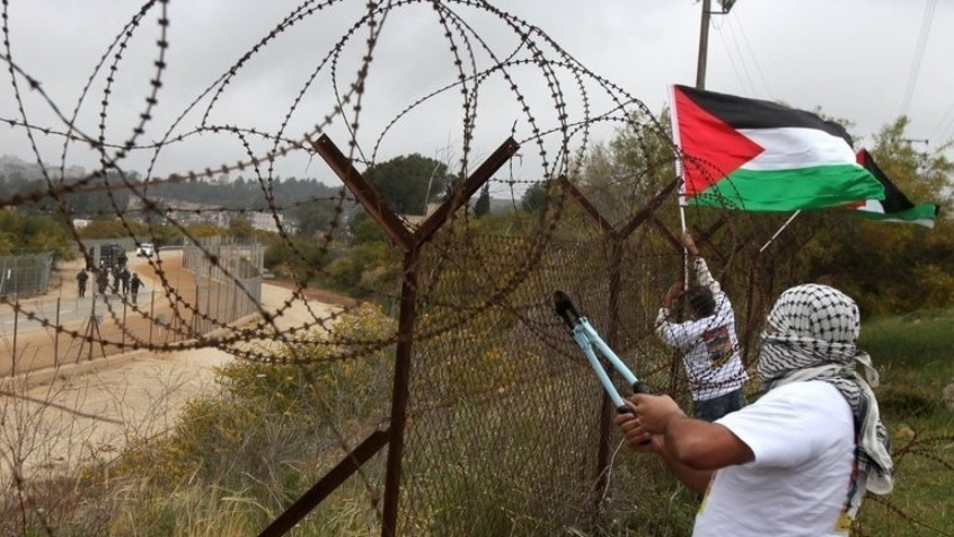 A protester cuts barbed wire as Palestinians mark Prisoners' Day next to Israel???s Ofer prison, on April 17, 2013.