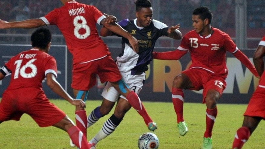 Liverpool's Raheem Sterling (C) vies with Indonesia national team players during a friendly football match at Bung Karno stadium in Jakarta on July 20, 2013. Liverpool won 2-0.