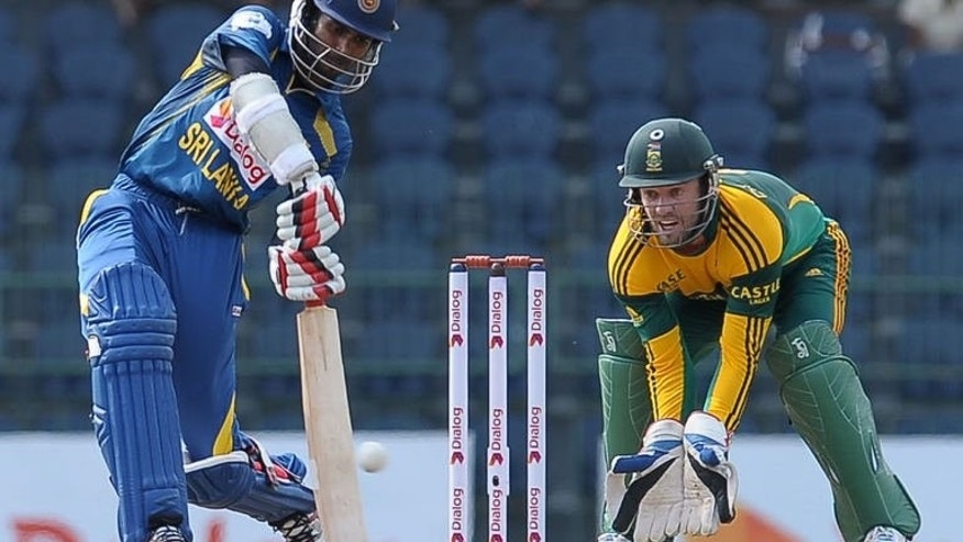 Sri Lankan batsman Upul Tharanga (left) is watched by South African wicketkeeper AB de Villiers as he plays a shot during their first One Day International in Colombo on July 20, 2013. Villiers won the toss and sent Sri Lanka in to bat.