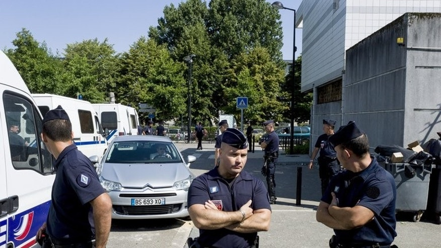 French policemen stand next to a police station in Trappes, a suburb of Paris, on July 20, 2013. A 14-year-old boy has been seriously injured in clashes between police and protesters in the western suburbs of Paris after officers stopped a woman for wearing a veil.