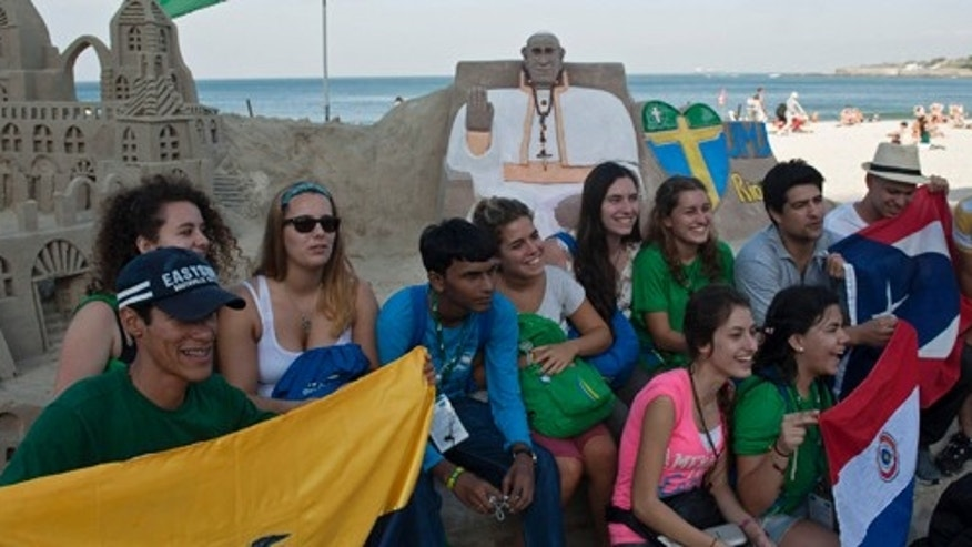 Catholic youth pose for a photograph in front of a sand sculpture of Pope Francis on Copacabana beach, in Rio de Janeiro, Brazil, Friday, July 19, 2013. Thousands of young Roman Catholics from around the Americas are converging on Rio de Janeiro to attend World Youth day, taking days-long bus trips or expensive plane flights that were paid for by baking cookies and holding garage sales, running raffles and bingo tournaments and even begging for coins in public plazas. (AP Photo/Nicolas Tanner)