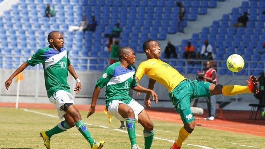 South Africa's Potlone Mabuti (R) clashes with Lesotho's Mkhwanazi Buhle (C) and Chabangu Lerato during a Cosafa Cosafa play off football match at Levy Mwanawasa Stadium in Ndola, on July 20, 2013. South Africa defeated tournament giantkillers Lesotho 2-1 to finish third.