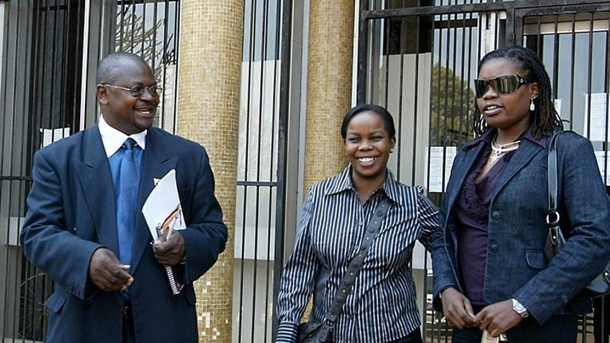 (From L-R) Rights lawyer Arnold Tsunga, with journalists Kundai Mugwano and Isabella Matambanadzo, leave court in Harare, on September 25, 2006. Zimbabwean police on Saturday arrested the prominent rights lawyer running for parliament against President Robert Mugabe's party in July 31 polls, a lawyers group said.